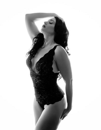 Black and white portrait of a black haired woman in a black body suit posing against a white background at boudoir and pinup by Janet Lynn Photography