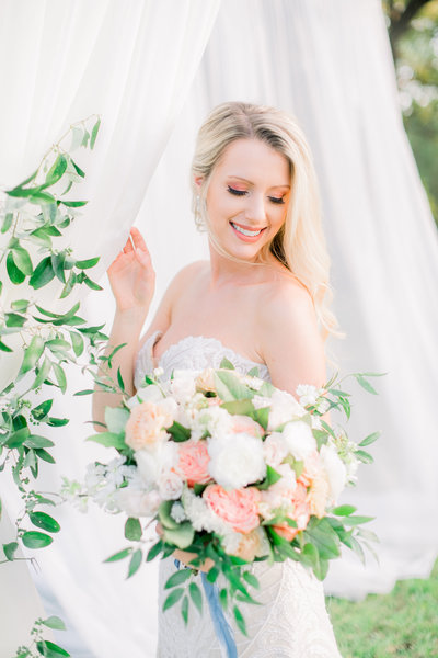 blonde bride against ivory drapery with greenery looking down to the side holding her pastel colored bouquet by atlanta wedding photographer lane albers photography