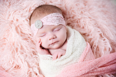 Beautiful newborn photography: Newborn girl wrapped in pink, ivory and rhinestones