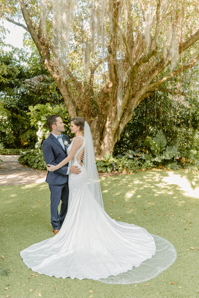 Bride and groom embrace underneath trees at Killian Palms Country Club