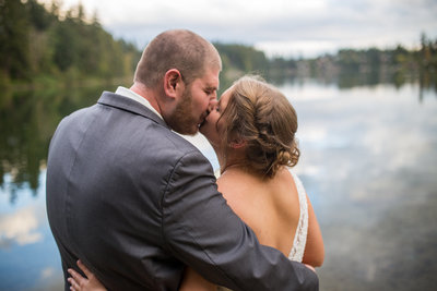Bride and groom hugging and kissing by the water at Lake Wilderness in Washington