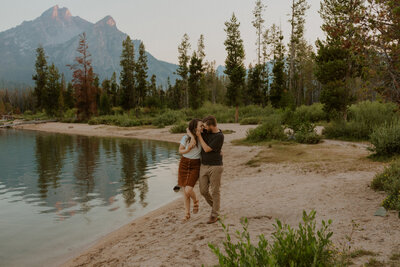 man and woman kissing in front of mountains