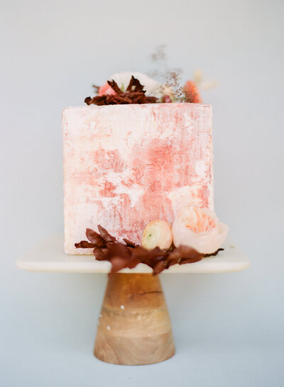 Peach square wedding cake with a concrete texture and fall floral accents