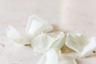 gold and diamond engagement ring on white rose petals