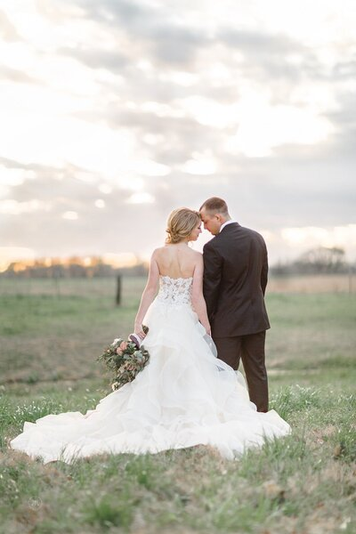 A bride and groom standing in a field at sunset.  They are facing each other and the bride has her bouquet at her side