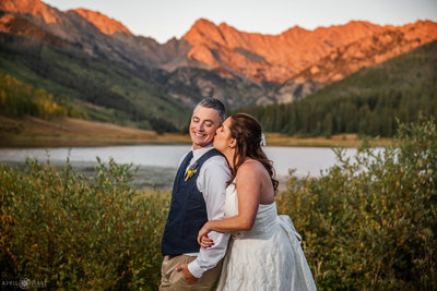 Bride and Groom Kiss with gorgeous orange sunset mountain backdrop at Piney River Ranch