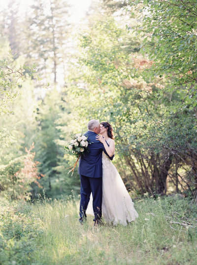 bride and groom kissing in montana forest