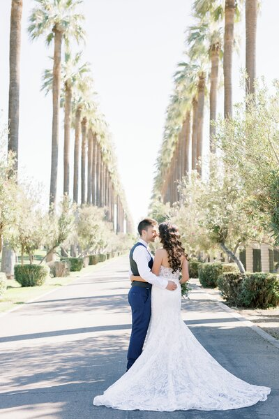 Bakersfield Wedding Photographer, Marianne Lucas. Bride & groom pictures in the driveway of Stockdale country club lined with tall palm trees.