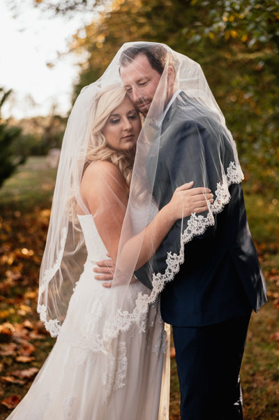 A bride and groom embrace under a wedding veil