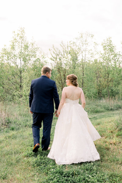 A bride and groom walk along a path in a garden at sunset and smile at each other