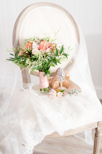Wedding bouquet and shoes sit on chair.