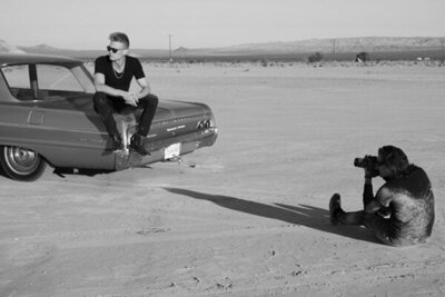 Behind the scenes photo Mark Maryanovich on ground in desert photographing musician Ryan Guldemon as he sits on trunk of vintage car wearing sunglasses and looking over his shoulder black and white image