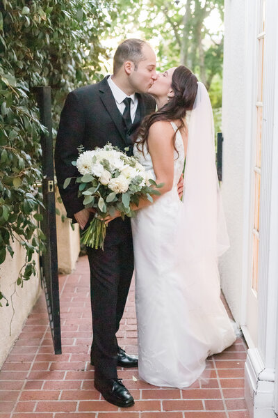 a bride and groom share a kiss following their wedding ceremony at the Vizcaya Sacramento in downtown Sacramento by Adrienne and Dani Photography