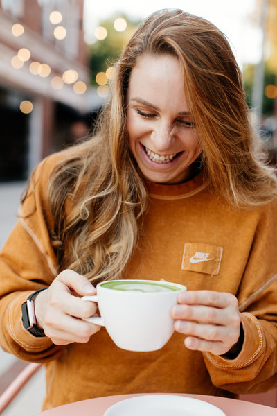 woman smiling and holding coffee mug