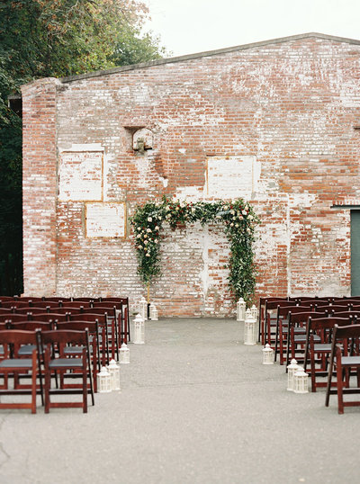 Full, lush greenery and bold flowers on this wedding arch with an industrial brick backdrop.