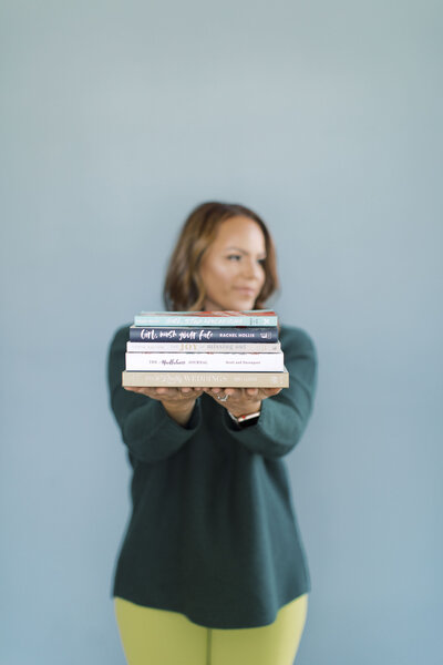 Female creative business owner with stack of books