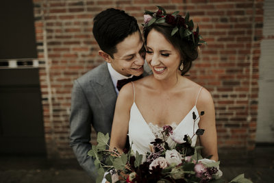 Bride and Groom smiling holding wild burgundy bouquet