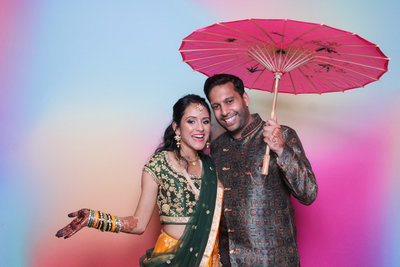 indian couple posing fron of a colorful backdrop