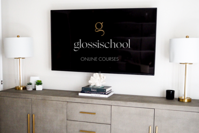 Glossischool online courses for makeup artists on large tv screen on a wall above a credenza