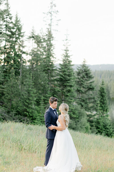 bride and groom facing each other with trees and mountains behind them in Cle Elum Washington
