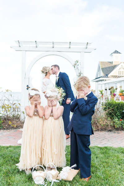 Flower girls and ring bearer cover eyes while bride and groom kiss