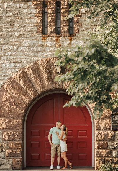 man and woman kissing in front of large red doors