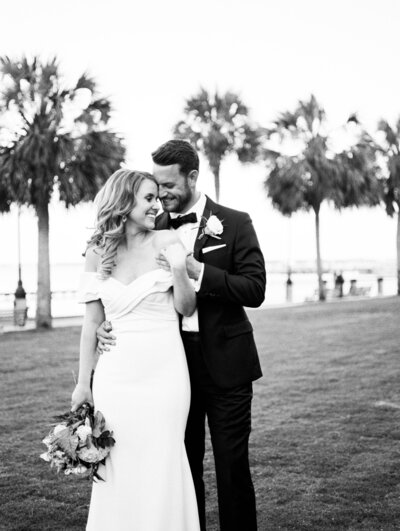 Groom embraces his bride on a lawn in front of palm trees at their Charleston wedding