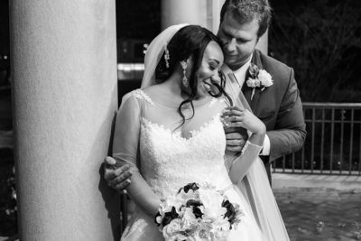 Bride and groom snuggle next to a column at Laughlin Memorial Library