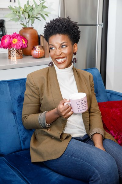 Woman sitting on a blue couch holding a pink mug, wearing a blazer