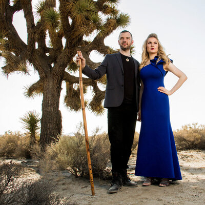 Music Portrait Duo standing next to joshua tree in desert Jason Campbell holding long wood flute hand Robin Campbell in blue dress with on hip