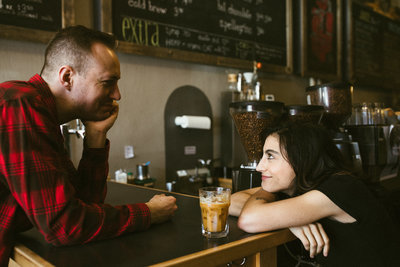 Married photographer duo Mike and Mandi look at each other over a bar, smiling.