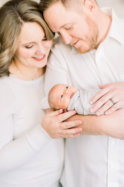 indoor close up family photo of a couple holding their newborn daughter  by atlanta wedding photographer lane albers photography