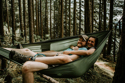 man & woman sitting in hammock