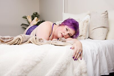 woman with purple hair laying on a bed posing for a boudoir photo