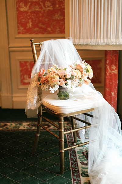 pastel bridal bouquet by roots floral design styled with a lace detailed bridal veil on a chair at the brown hotel wedding
