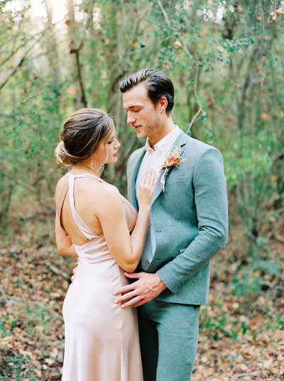 Tender bride and groom portrait with an open back peach wedding dress and loose coiffured updo