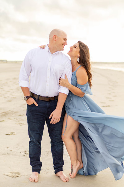 Future husband and wife looking into each others eyes on Florida beach at sunset photo session in a white dress shirt and flowy blue engagement session dress