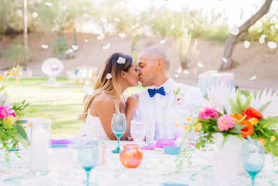 bride and groom wearing white kissing at head table