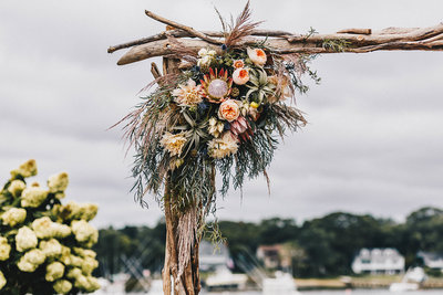 Unique outdoor wedding ceremony arch with flower bouquet in the corner