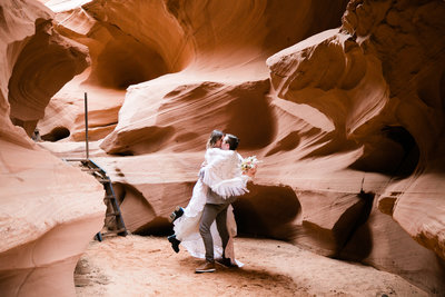 This eloping couple celebrates in a slot canyon. The groom picks his bride up off her feet and swings her around.