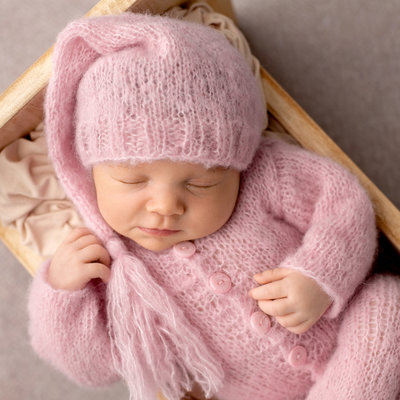 newborn girl smiles dressed in pink