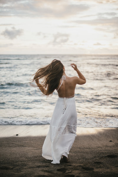 Woman wearing white dress walking on beach toward ocean