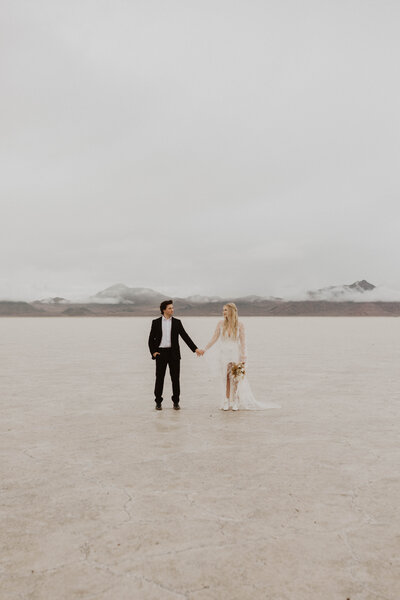 Couple holding hands and looking at each other at the salt flats with mountains in the background