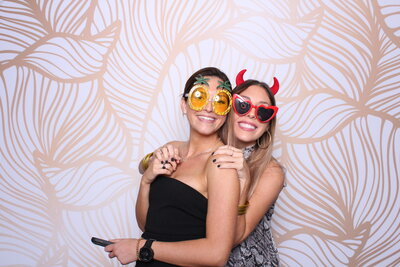 Two ladies posing in front of the photo booth with island props in front of a tropical gold and white backdrop at the don cesar in st petersburg fl