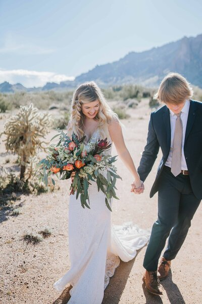 Gatlinburg Photographer Bride and groom hold hands as she holds bouquet in desert