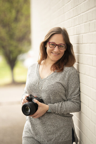 Female Photographer smiling with camera in hand