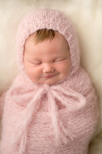 newborn baby girl swaddled in pink smiles for portrait on blue fur