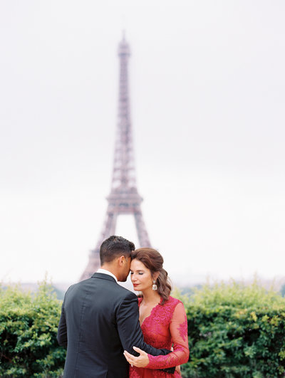 Couple embraces in front of Eiffel Tower during Paris anniversary photography session