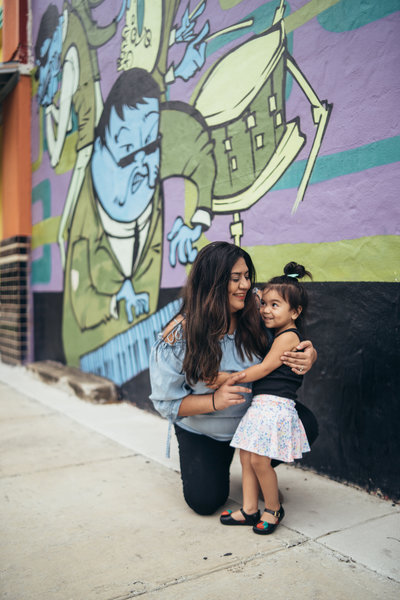 Photo of San Antonio Wedding Photographer Irene Castillo holding her daughter while posing for a picture