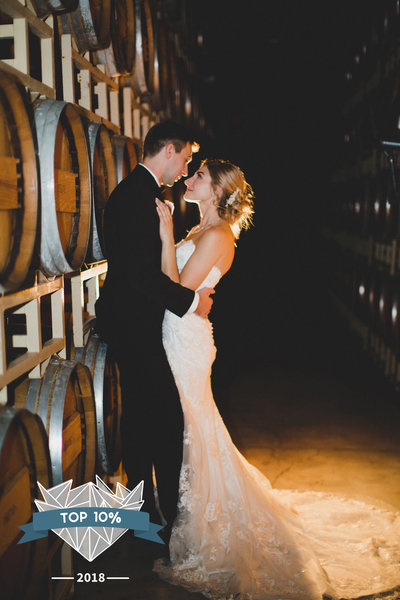 Bride and groom hugging in front of wine barrels